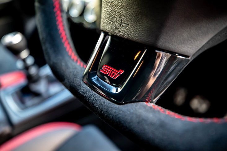 The SAIGO WRX features a suede D-shaped steering wheel with a STI logo.