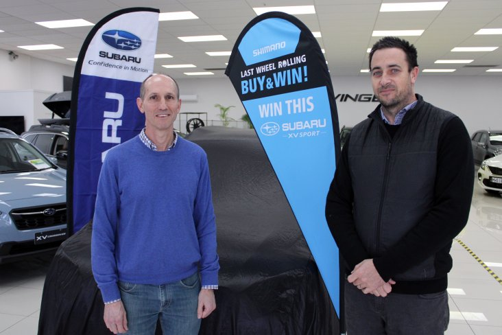 The lucky winner of the Last Wheel Rolling promotion's first prize Charles Oram (left) waits for his Subaru XV Sport to be revealed by Shimano NZ's GM Ben Ashby.
