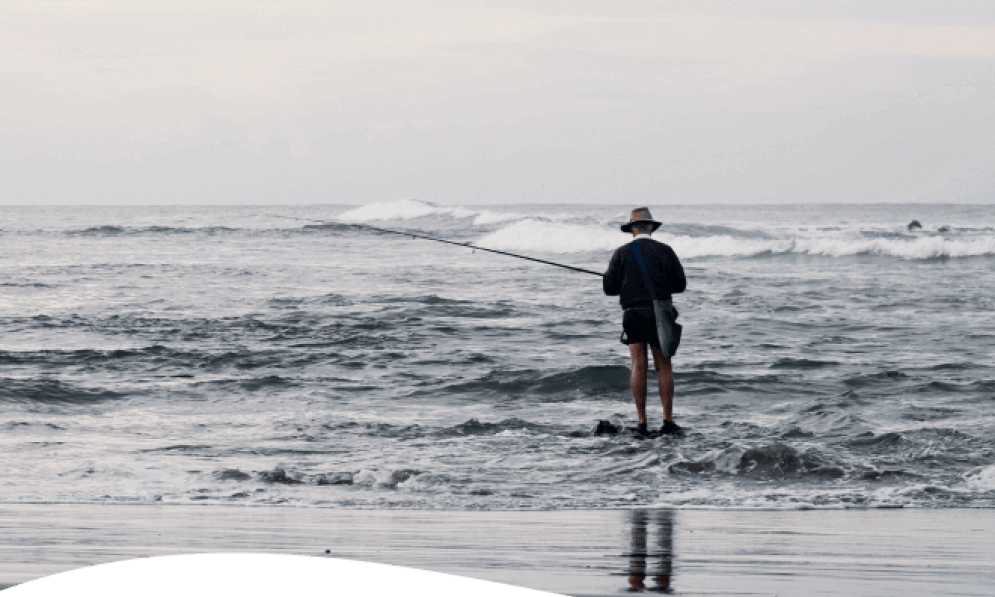 Man fishing in shallows at surf beach